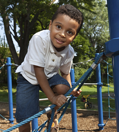 Photo of boy playing on a jungle gym made of ropes