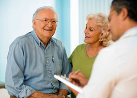 Photo of older couple speaking to physician