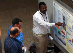 Photo of Ailton Coleman discussing his research with Brandon Albright and Kareem Mohni