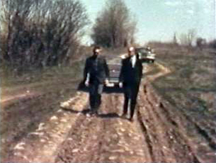 Two men walking down a dirt road toward the construction site