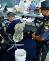 Photo of a Health Center police officer and a volunteer handling a prescription medication vial