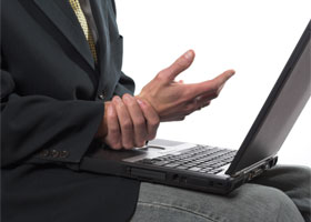 Photo of a man with a laptop holding his wrist