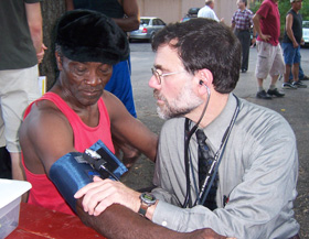 Dr. Bruce Gould examines a seasonal worker at the Thrall Tobacco Farm in Enfield in July of 2007, providing care as a physician with the Mobile Free Migrant Farm Workers Clinic.